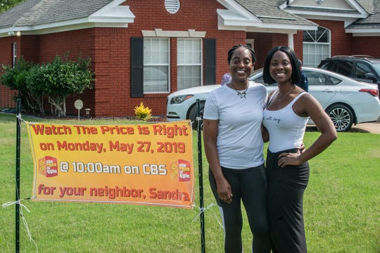 "Sandra H. Glenn, left, of Montgomery and daughter Natasha Normal of California stand next to a banner outside Glenn's home in Montgomery. In December 2018, Glenn went on ""The Price Is Right,"" and won. Her episode aired on Monday, May 27, 2019."