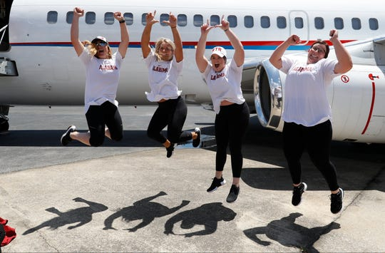 Members of the Alabama softball team celebrate arriving in Oklahoma City on Tuesday, May 28, 2019, for the Women's College World Series.