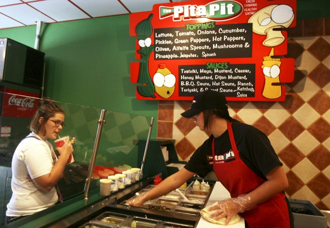 From 2006: Pita Pit employee Beth Carson fixes a pita for Ball State University student Jaclyn Wall Saturday afternoon. Photo by Melanie Maxwell
