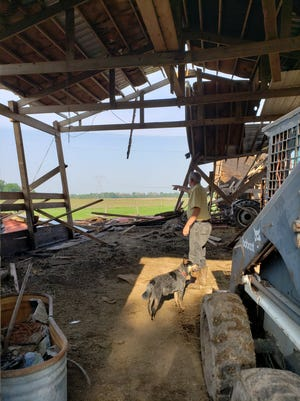 Larry Sanders points to where the southwest corner of the barn used to be, before Monday's storm destroyed the barn and left little more than a single wall and partial roof remaining.