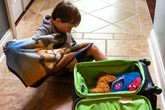 Thomas Peppers, 5, packs his suitcase for a pretend vacation with a stuffed animal, blanket and pillow at his Franklin home Thursday, May 23, 2019. The oldest three Peppers children were provided suitcases to replace the trash bag that held their belongings while they were in foster care.
