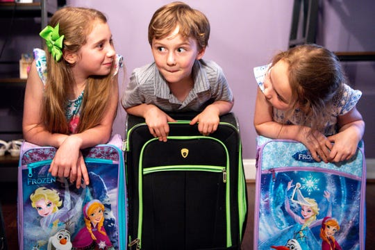 Becca, 9, Thomas, 5, and Sammie Peppers, 7, from left, pose for a portrait with their suitcases at their Franklin home Thursday, May 23, 2019. The oldest three Peppers children were provided suitcases to replace the trash bag that held their belongings while they were in foster care.