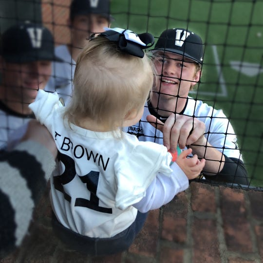 Vanderbilt pitcher Tyler Brown grins at his daughter, Isabella, before a Commodores baseball game at Hawkins Field.