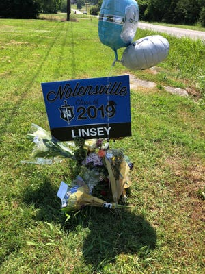 Flowers and balloons surround Stewart's graduation yard sign.