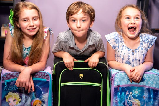 Becca, 9, Thomas, 5, and Sammie Peppers, 7, from left, pose for a portrait with their suitcases at their home Thursday, May 23, 2019, in Franklin, Tenn. The oldest three Peppers children were provided suitcases to replace the trash bag that housed their belongings while they were in foster care.