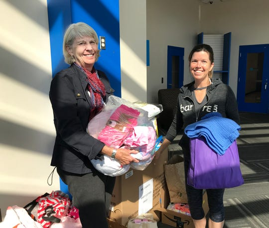 Lena Levendoski, right, and Mary Hance look over the donated baby clothes that were dropped off at The Tennessean offices in April 2019.