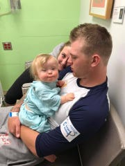 Vanderbilt pitcher Tyler Brown holds his daughter Isabella before one of her two heart surgeries. Isabella's mother, Jocelynn Butcher, sits with them in the hospital.
