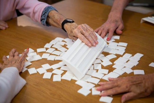 Annette Malefyt uses her tile rack to help mix up the tiles between rounds of Rummikub with Catherine Allen, left, Katherine Dixon, center right, and Doris Flaitz, right, at Life Care Center of Estero on Wednesday, May 22, 2019.