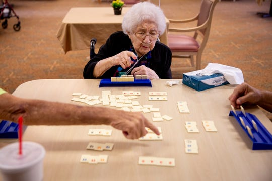 Pauline Pelkey, 101, center, directs Paul Jorden, left, and Mike Allette, right, on where to place her tiles as they play Rummikub at Life Care Center of Estero on Wednesday, May 22, 2019. Pelkey says that her favorite part about playing Rummikub is winning.