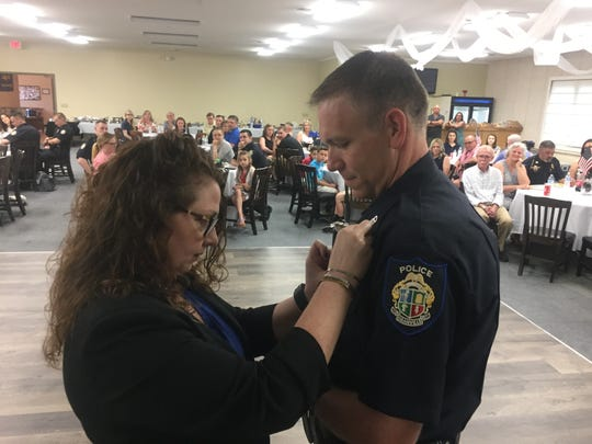 New Granville Police Officer Martin Kaffenbarger receives his badge from his wife, Sarah.