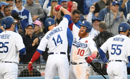 Los Angeles Dodgers center fielder Enrique Hernandez (14) celebrates with third baseman Justin Turner (10) after hitting a three run home run against the New York Mets in the sixth inning at Dodger Stadium.
