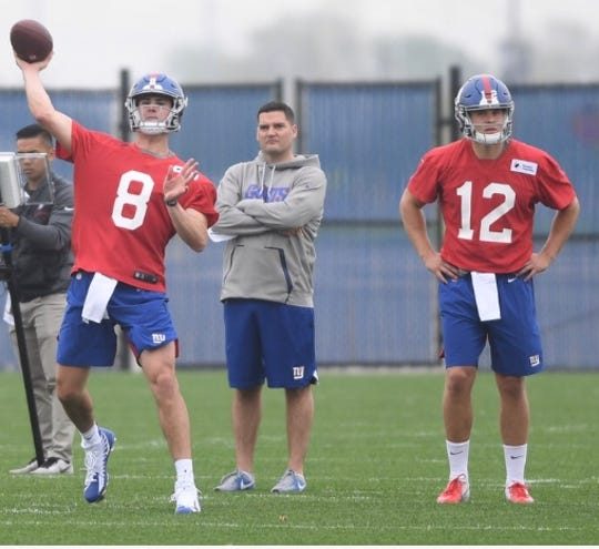 """Giants rookie Eric Dungey (12) and assistant coach Ryan Roeder, center, watch first-round pick Daniel Jones (8) throw a pass during rookie camp in East Rutherford. Dungey, a quarterback at Syracuse, is trying to make the team as """"a football player,"""" switching positions to tight end while hoping to contribute on special teams to show his versatility."""