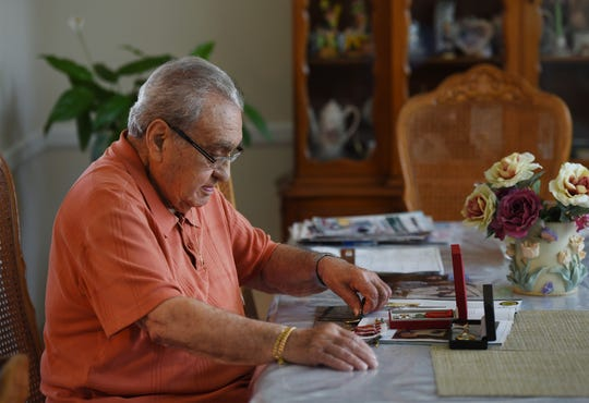 """John Santillo (age 97) of Brick, former member of 237th Engineer Combat Batallion US, Army, who was onboard one of the landing crafts landed on Normandy's Utah Beach on June 6 1944 known as """"D-Day"""", looks at some of his memorabilia including the metal, the French Legion of Honor, at his home in Brick on 05/24/19."""