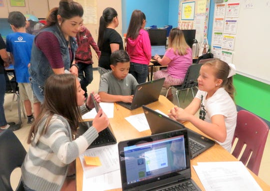 Deming Intermediate Middle School Principal, Charlotte Sandoval, secretary, Terrie Martinez, and Infinite Campus Representative, Sarah Krowl, visited Bataan Elementary School fifth graders last week to help them register for electives in Infinite Campus. Sandoval visited with over 90 students from Gina Simms's, Doris Lancaster's, Melissa Noriega's, and Kim Perea's fifth-grade classrooms. Standing at left is secretary, Terrie Martinez assisting students from Perea's classroom, while Krowl distributes identification numbers and passwords to all the students.