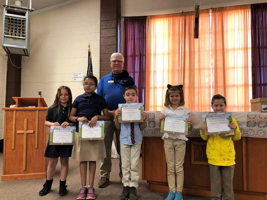 Ned Kline (of Alamogordo Kiwanis Club with five of St. Frances Cabrini School's 32 BUG Honor Roll students.