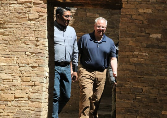 Pueblo of Acoma Gov. Brian Vallo, left, and U.S. Interior Secretary David Bernhardt walk through a room Tuesday at Chaco Culture National Historical Park in northwestern New Mexico.