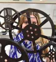 Brittany Smithkort peers through some decorative film reels she keeps in her South Lyon High classroom.