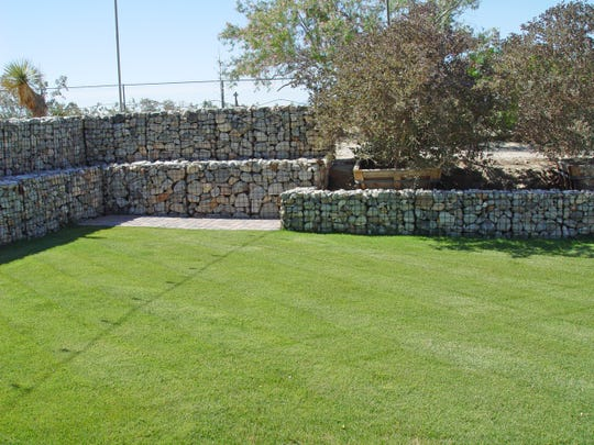 A low gabion continues as a seawall to keep particles from flowing down onto the lawn from the cut slope behind.
