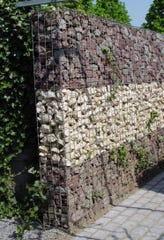 A battered, freestanding gabion is filled with volcanic rock in this European example.