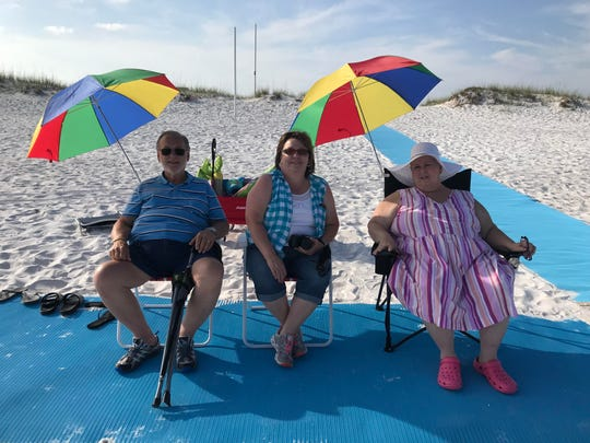 At right, Cheryl Cardwell, who was diagnosed with terminal cancer in October 2018, was able to realize her dream of going to the beach thanks to Navarre Beach's Mobi Mats. She is pictured here with her sister, Carol Melton, center, and father, Charles Wood, left.