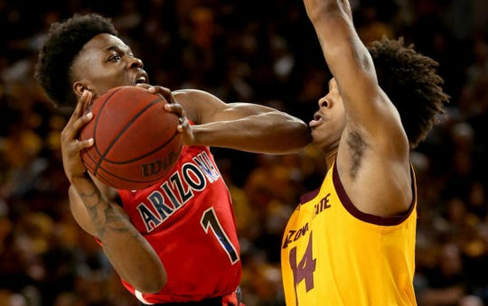 Arizona guard Devonaire Doutrive (1) elbows his way through Arizona State forward Kimani Lawrence (14) in the second half of their Pac-12 game at Wells Fargo Arena, Thursday, January 31, 2019, Tempe, Ariz.