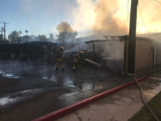 Firefighters work to put out a fire that started in a parking structure on May 28, 2019.
