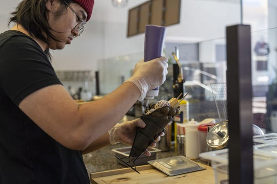 Matthew Wong, owner of Genbu Waffles in Mesa, dishes up a creation. The East Valley has the largest Asian American population in the Phoenix area, and more Asian-owned businesses are popping up in Mesa and Tempe.