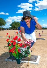 Margaret Duran of Phoenix lays flowers at the grave of her brother, U.S. Navy veteran Armando Rodriguez during Memorial Day ceremonies at the National Memorial Cemetery of Arizona.