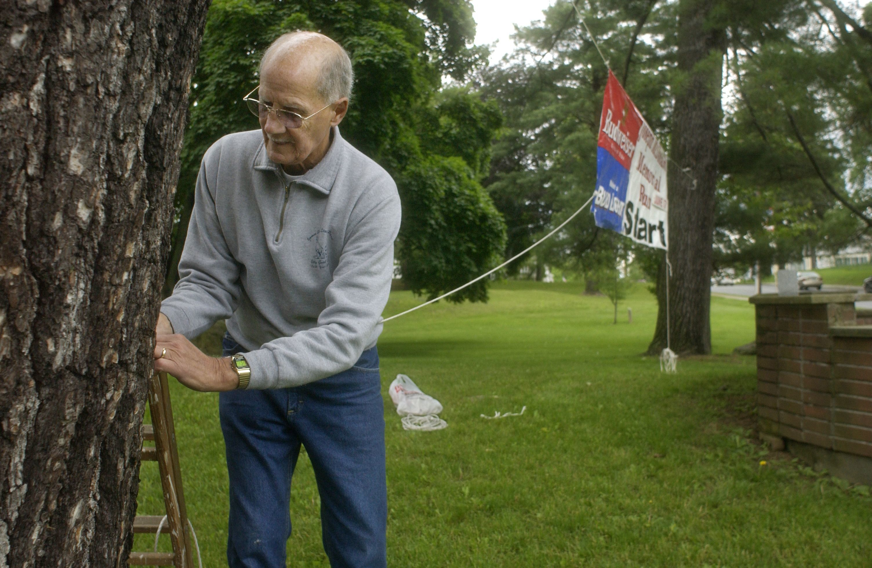In this June 2006 file photo, Pete Sanfilippo hangs a banner for the Joseph McDonald/Bill Crusie Memorial Run in Mesier Park in the Village of Wappingers Falls. Sanfilippo, who died in 2016, will be honored during the June 1 event, which he established during the late 1970s.