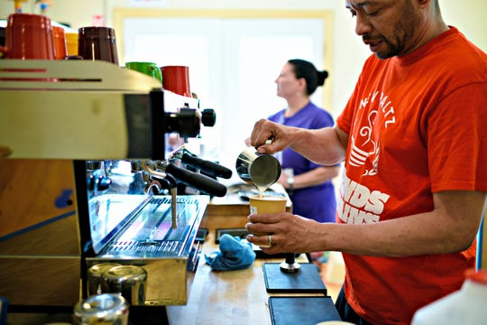 RashidChambers, co-owner of Grinds & Grains in New Paltz, prepares a cup of coffee.