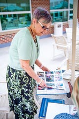 Martha Thomas pages through photo albums that she keeps to remember each and every unique delivery she performed.