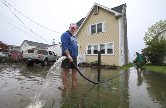 "Eric Eagan uses a hose to help pump out water from his flooded basement on Cranberry Drive in Greece Tuesday, May 28, 2019 in Rochester.  Massive flooding from rising Lake Ontario has left homeowners all along the Greece shore scrambling. ""There's a waterfall in my basement"" said Eagan."