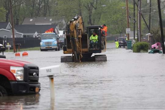 Heavy machinery is called in to install pumps in waist-deep water on Edgemere Drive in Greece on Tuesday.