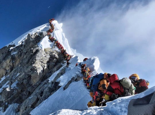 In this photo made on May 22, 2019, a long queue of mountain climbers line a path on Mount Everest. About half a dozen climbers died on Everest last week most while descending from the congested summit during only a few windows of good weather each May. (Nirmal Purja/@Nimsdai Project Possible via AP)