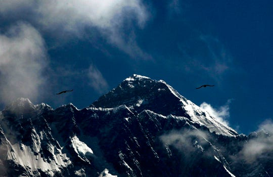 In this Monday, May 27, 209, photo, birds fly as Mount Everest is seen from Namche Bajar, Solukhumbu district, Nepal. Seasoned mountaineers say the Nepal government's failure to limit the number of climbers on Mount Everest has resulted in dangerous overcrowding and a greater number of deaths. (AP Photo/Niranjan Shrestha)