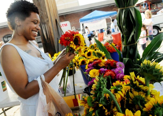 Margaret Matthews buys flowers at the Shreveport Farmer's Market.