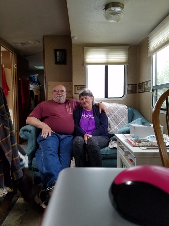 Darlene Albrecht (right) sits with her husband in their camper.