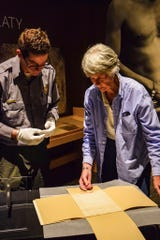 """This June 6, 2018, photo provided by the New Mexico Historic Sites shows Clare """"Kitty"""" Weaver, right, and Fort Sumner Historic Site Manager, Aaron Roth preparing the Navajo Treaty of 1868 for display for the 150th Commemoration of its signature at Bosque Redondo Memorial at Fort Sumner, N.M. (New Mexico Historic Sites via AP)"""