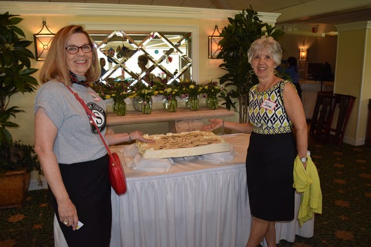 Carol Stewart Langes, left, and Jane Cebelak show off the celebratory cake at the United Way of Martin County RSVP Volunteer Appreciation Luncheon.