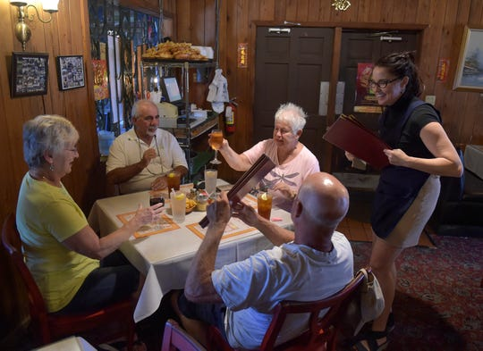 "Waitress Jana Gittelman (right) collects the menus from Szechuan Palace customers (clockwise from left ) Pat and Nick Georges, and their friends Missi and David Light, as they prepare for lunch at the restaurant on Tuesday, May 28, 2019 in Vero Beach. After 30 years, the popular Chinese restaurant is closing its doors, their last day is June 15th, as the owners Sue and John Liang retire. ""I'm sad it's closing, it will be missed,"" Missi Light said. ""Wonderful prices, friendly people, lovely old building."""
