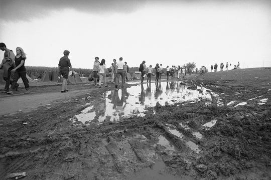 Rock music fans hike from the Woodstock Music and Art Festival in Bethel, New York, Aug. 17, 1969. Some 300,000 fans began to leave as the festival ended in the rain.