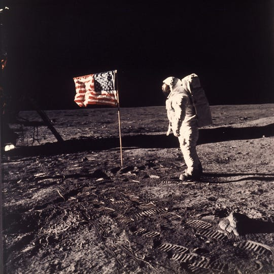 "Astronaut Edwin E. ""Buzz"" Aldrin Jr.  poses for a photograph beside the U.S. flag deployed on the moon during the Apollo 11 mission on July 20, 1969.  Aldrin and fellow astronaut Neil Armstrong were the first men to walk on the lunar surface with temperatures ranging from 243 degrees above to 279 degrees below zero.  Astronaut  Michael Collins flew the command module.  The trio was launched to the moon by a Saturn V launch vehicle at 9:32 a.m. EDT, July 16, 1969. They departed the moon July 21, 1969."