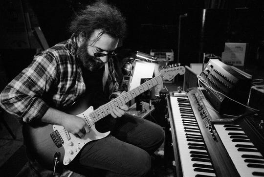 """Jerry Garcia, leader of the legendary group The Grateful Dead, works with his guitar on May 8, 1979. At the time of the Woodstock Festival, many groups had an uncertain future. """"Musically, it was a total disaster for us,"""" Garcia said of Woodstock in a interview. """"I remember people standing in back of us yelling the stage is falling down. Plus it was wet for so long and we had all that electronic equipment."""""""