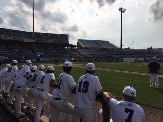 Caravel Academy players watch from their dugout at Frawley Stadium Tuesday.