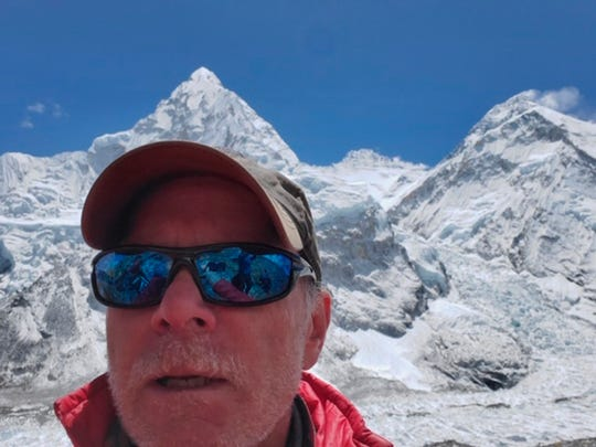 This April 2019 selfie photo provided by Mark Kulish shows his brother Christopher Kulish beneath Mount Everest.