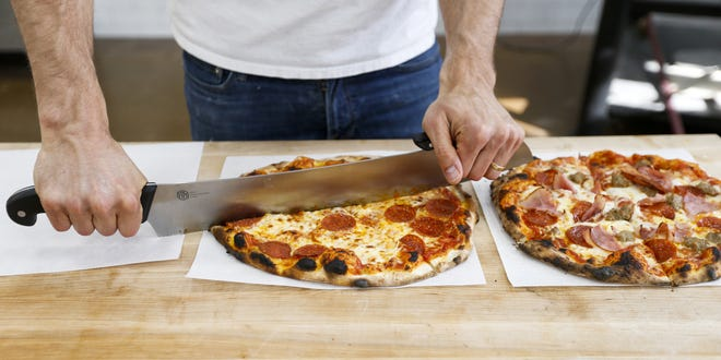 Paul Wise slices a pizza fresh from the brick oven at Christianos Pizza in Appleton. The new pizzeria is the fifth owned by the Wise family.