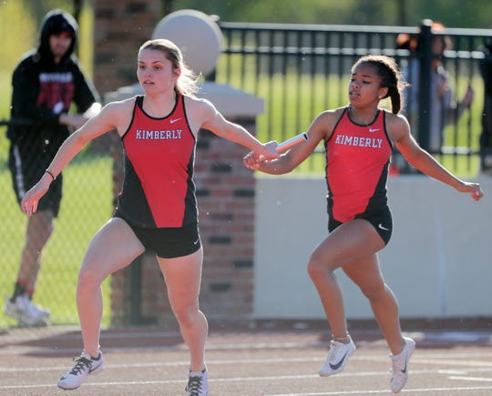 Kimberly's Amaija Powell hands the baton to Taylor Hietpas in the 800-meter relay at a WIAA Division 1 track and field sectional in De Pere on May 23.
