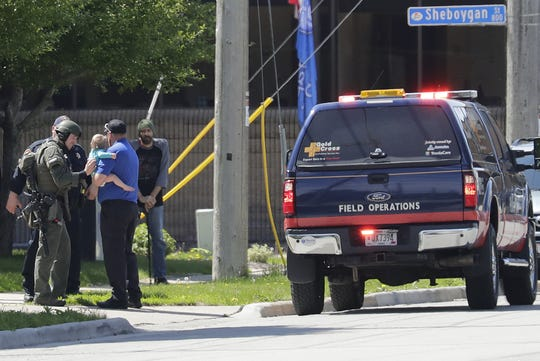 Police hand over a child Wednesday, May 29, 2019, at Manitowoc and Fifth streets in Menasha.
