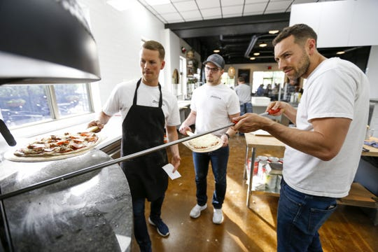 Sean Wise, left, Lucas Dutcher and Paul Wise work with the massive wood-fired brick oven at Christianos new Appleton location. The restaurant, now open, is the fifth owned by the Wise family.