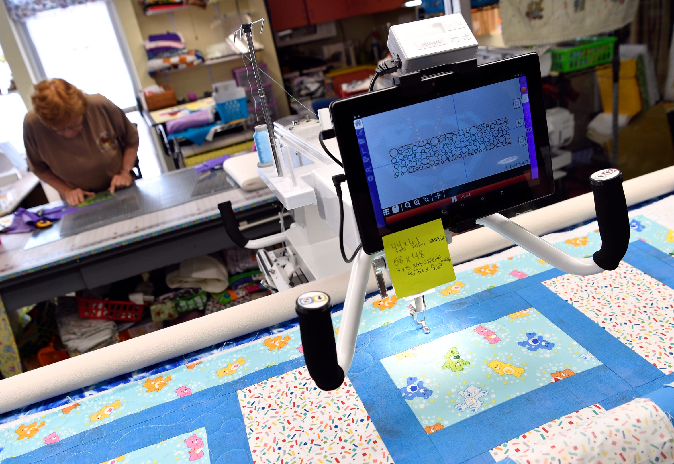 A computer-controlled machine stitches a pattern into a quilt as Linda Christiansen works on her own project in the background at R Quilt Haven on May 14.